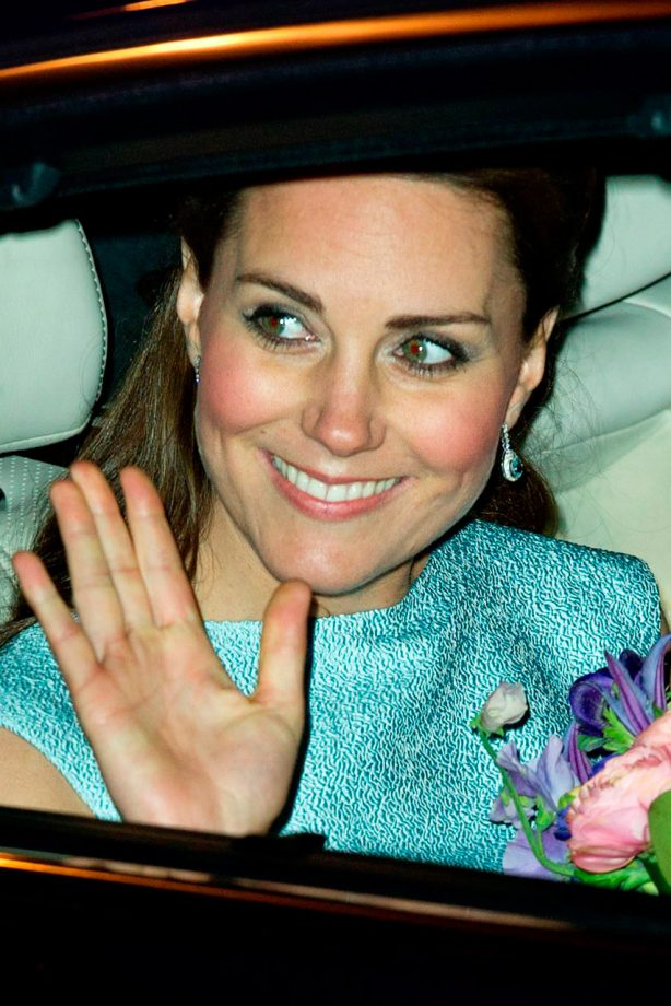 Kate Middleton wears a green dress and holds flowers as she's driven away