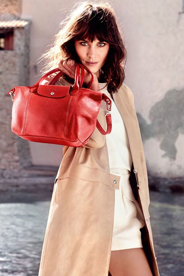 Alexa Chung wears a white dress and models the bright red leather tote for Longchamp's Spring 2014 ad campaign