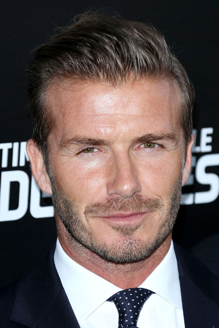 David beckham wears a black suit and tie at a London premiere