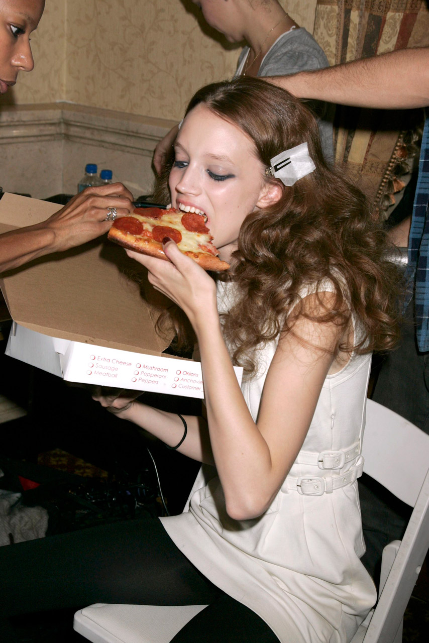 model eating pizza