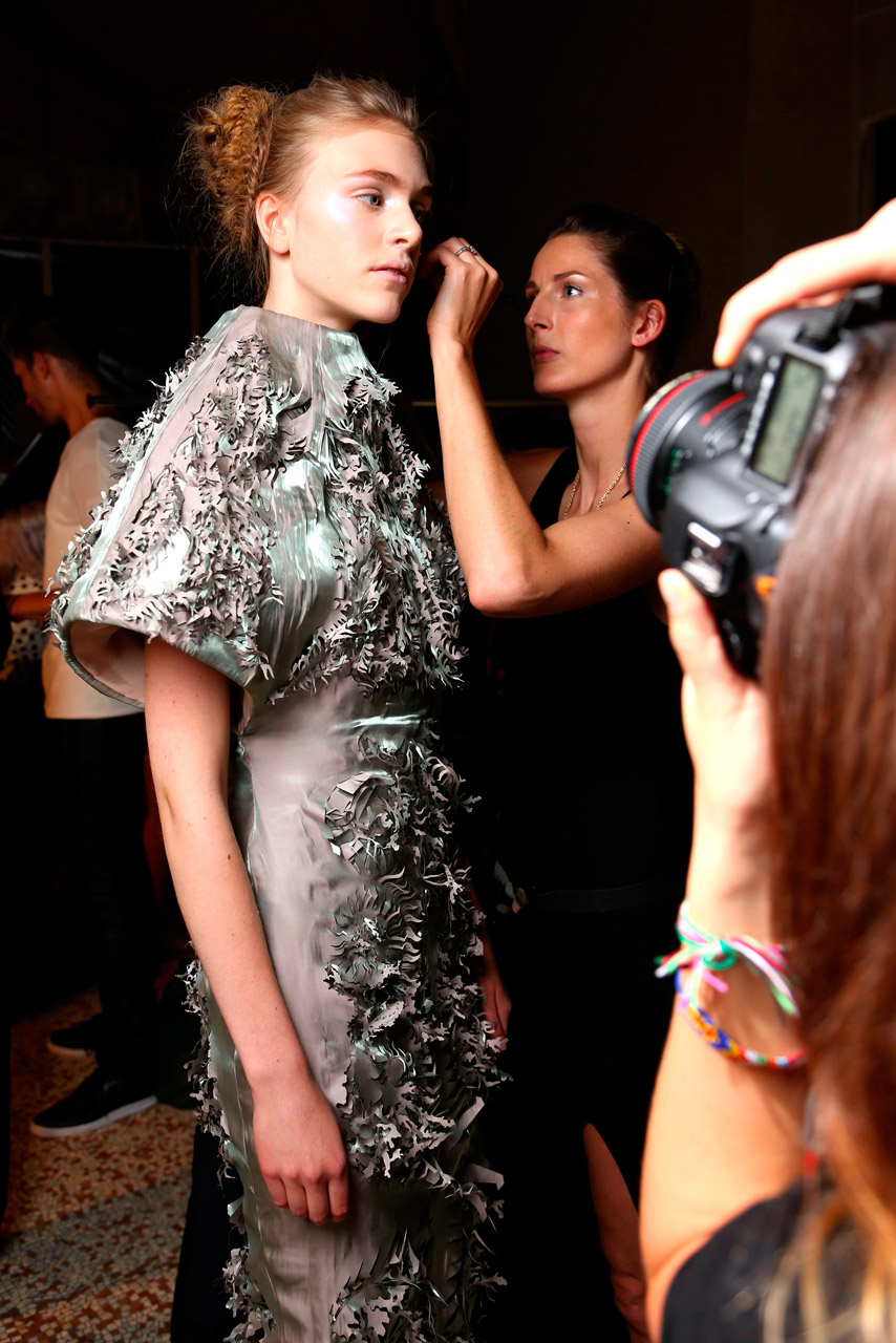 model getting make-up touched up backstage