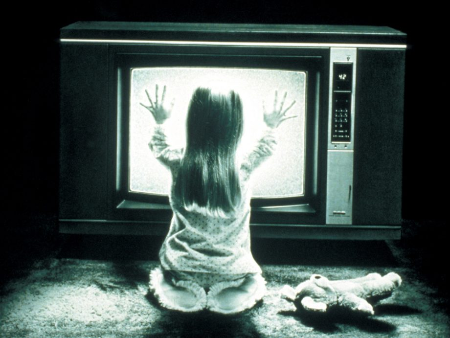 Girl sitting in front of bright white screen television and putting hands against screen