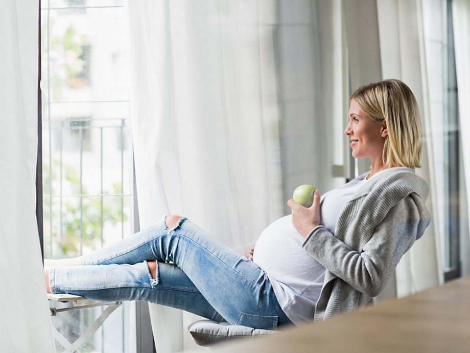 Full term pregnancy young woman eating apple