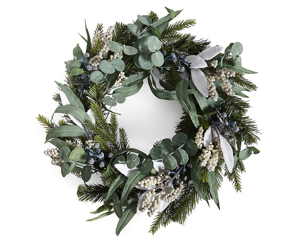 this faux wreath strays away from bright coloured berries and florals in exchange for a mix of textures from fir branches to white berries