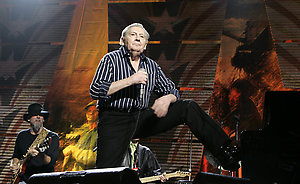 Jerry Lee Lewis plays the piano with his boot as he sings at the Farm Aid concert in Camden, N.J., Saturday, Sept. 30, 2006. (AP Photo/Mel Evans)