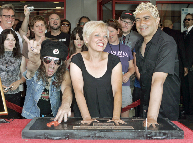 The three surviving members of the '70s punk band The Germs, from left, Don Bolles, Lorna Doom and Pat Smear, place their hand prints, and a crustacean claw print for Bolles, in the wet concrete of a plaque that will be installed in Hollywood's RockWalk in Los Angeles Wednesday, Aug. 20, 2008. The special plaque commemorates lead singer Darby Crash, who died in 1980. (AP Photo/Reed Saxon)