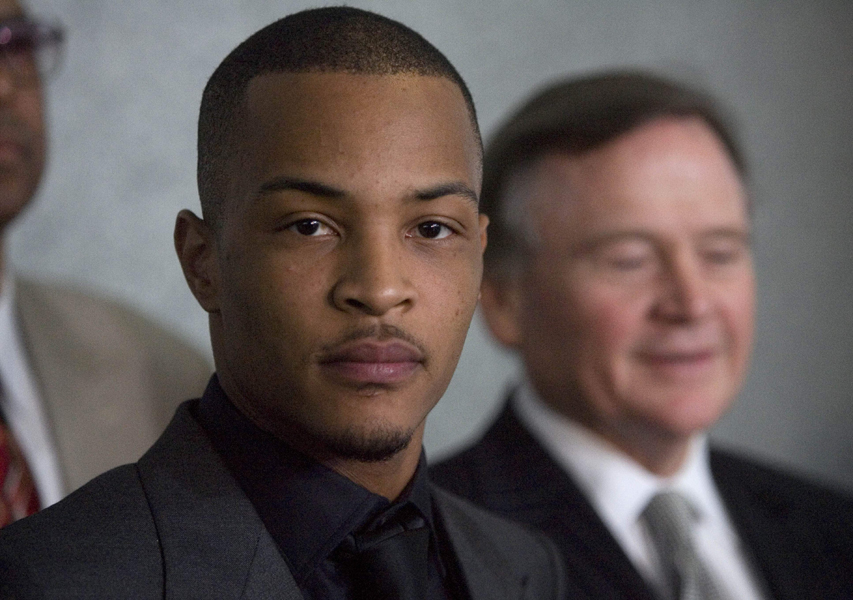 Rapper T.I., who's real name is Clifford Harris,stands for a press conference with attorneys Dwight Thomas, left, and Ed Garland, right, after being sentenced to one year and one day on federal weapons charges at the Federal Courthouse, Friday, March 27, 2009, in Atlanta. (AP Photo/John Amis)