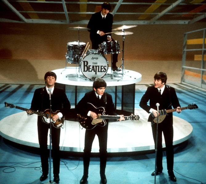 """The Beatles perform on the CBS """"Ed Sullivan Show"""" in New York Feb. 9, 1964. From left, front, are Paul McCartney, George Harrison and John Lennon. Ringo Starr plays drums. (AP Photo)"""