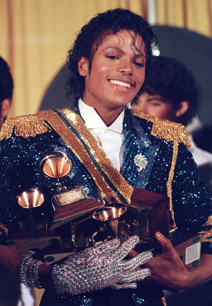 Michael Jackson is seen backstage at the 26th annual Grammy Awards in Los Angeles Tuesday, Feb. 28, 1984, as he poses with the awards he won in eight different categories. (AP Photo/Reed Saxon)