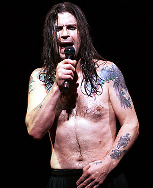 Ozzy Osbourne photographed performing live on stage in Milan, Italy. 3/4 length. . chest abs topless. tattoos
