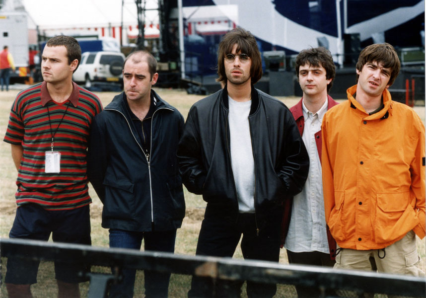 """7th MAY : On this day in 1995 rock group Oasis were top of the charts with their first number one, 'Some might Say'. The band Oasis line up before their Knebworth Park concert. (l-r) drummer Alan White, rhythm guitarist Paul """"Bonehead"""" Arthurs, lead singer Liam Gallagher, bass player Paul """"Guigsy"""" McGuigan and guitarist and songwriter Noel Gallagher.  * 25/8/99 :  The band have revealed that their bass player Paul 'Guigsy'  McGuigan (second right) is to leave the band.  Only two weeks after it was revealed that guitarist, Bonehead (second left) was leaving."""