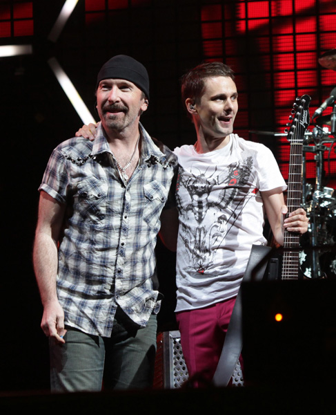 EDITORIAL USE ONLY NO MERCHANDISING. Matt Bellamy of Muse (right) with guest The Edge of U2 performing on the Pyramid Stage during the Glastonbury Festival in Somerset.