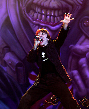 The singer of the British group Iron Maiden, Bruce Dickinson, performs in front of a poster during a concert in Barcelona, Spain, Thursday Nov. 30, 2006. (AP Photo/EFE, Alberto Estevez) ** LATIN AMERICA, CARIBBEAN AND SPAIN OUT **