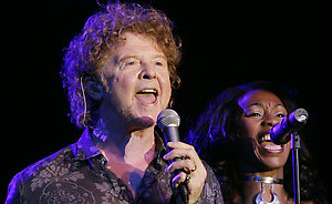 British band 'Simply Red' front man Mick Hucknall, left, and an unidentified background singer perform during a concert in Berlin on Wednesday, Aug. 16, 2006. The British band starts its Germany tour in Berlin on Wednesday. (AP Photo/ Jan Bauer)
