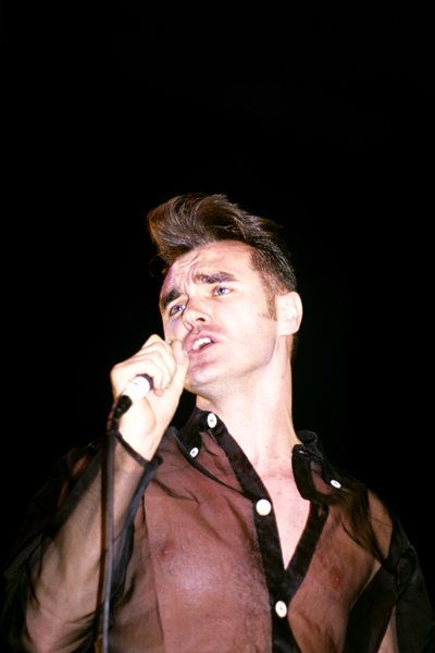Musician Morrissey singing on stage.