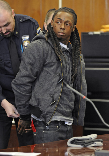 Rapper Lil Wayne is handcuffed at Manhattan criminal court, Monday, March 8, 2010, in New York, after being sentenced to a year in jail in New York City for having a loaded gun on his tour bus in 2007. (AP Photo/ Louis Lanzano)