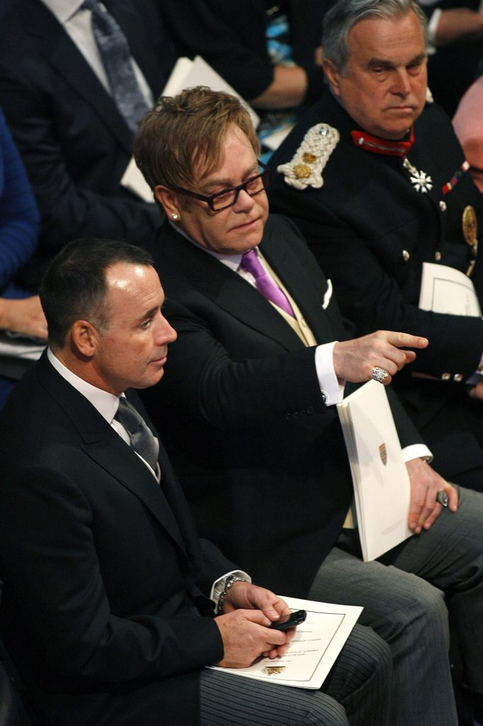 Elton John, center, and his partner David Furness, left, sit in Westminster Abbey, London ahead of the royal wedding between Britain's Prince William and Kate Middleton Friday April 29, 2011. (AP Photo/ Richard Pohle, Pool)