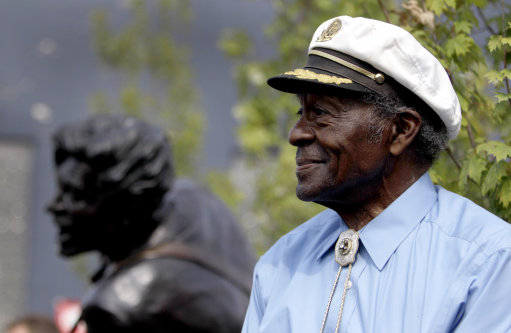 Legendary musician Chuck Berry sits on a stage next to a statue of himself during its dedication Friday, July 29, 2011, in University City, Mo. The statue of the St. Louis native was dedicated near Blueberry Hill, the University City club where the octogenarian still performs monthly. (AP Photo/Jeff Roberson)