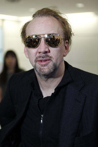 """Actor Nicolas Cage poses for photographers upon his arrival at Narita International Airport in Narita, east of Tokyo, Monday, July 19, 2010. Cage is here to promote his new film """"The Sorcerer's Apprentice"""". (AP Photo/Shizuo Kambayashi)"""