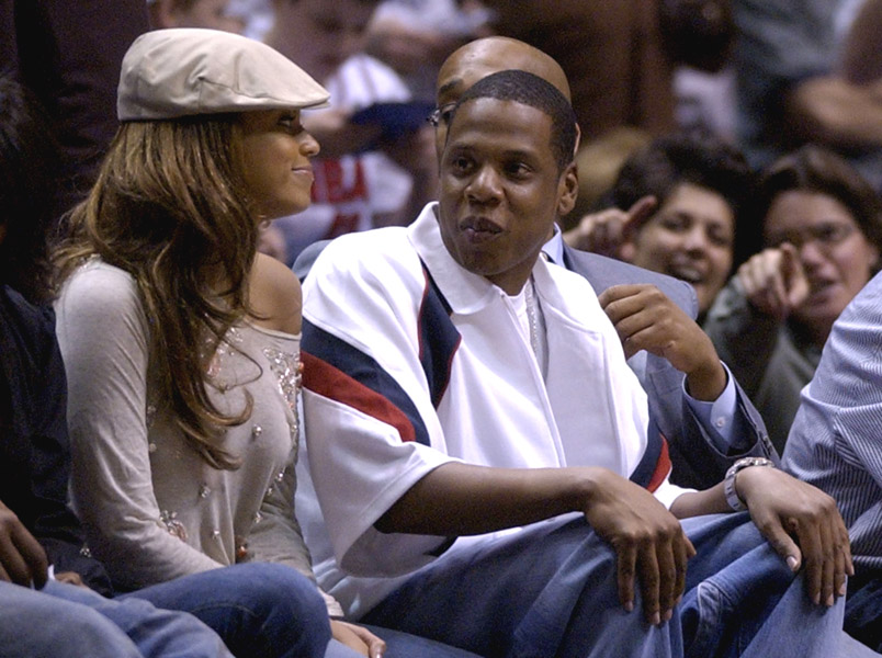 Music artists Beyonce Knowles, left, and Jay-Z sit on the sidelines while watching game four of the second round of the NBA playoffs between the Detroit Pistons and New Jersey Nets Tuesday, May 11, 2004 in East Rutherford, N.J.. (AP Photo/Julie Jacobson)