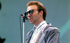 Ultravox singer Midge Ure performing on stage.