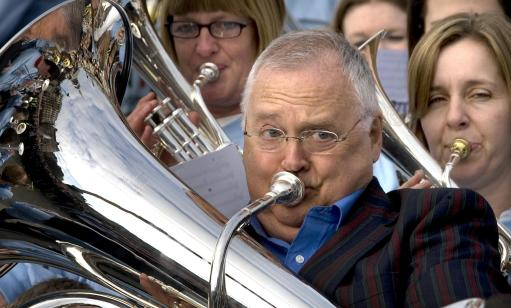 The theme tune of Australian soap Neighbours is performed by star Ian Smith (Harold Bishop), along with hundreds of brass band musicians from around the UK to celebrate its imminent arrival on Five TV, Trafalgar Square, central London.