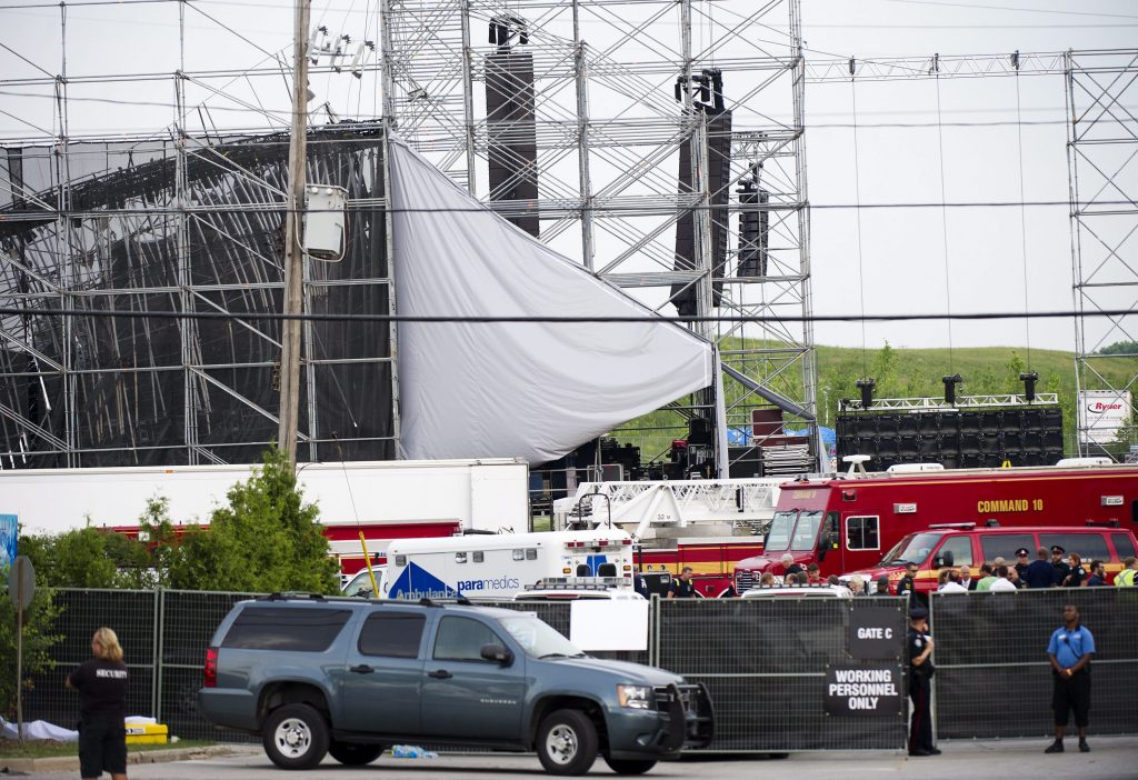 Emergency personnel work near the scene of a collapsed stage at Downsview Park in Toronto on Saturday, June 16, 2012. The top of a stage being set up for a concert by the band Radiohead collapsed, killing one of the stage workers preparing for the event. (AP Photo/The Canadian Press, Nathan Denette)