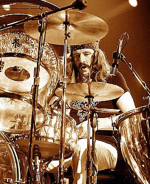 John Bonham performing live onstage, playing Ludwig Vistalite see-through acrylic drum kit, drums (perspex), wearing haedband