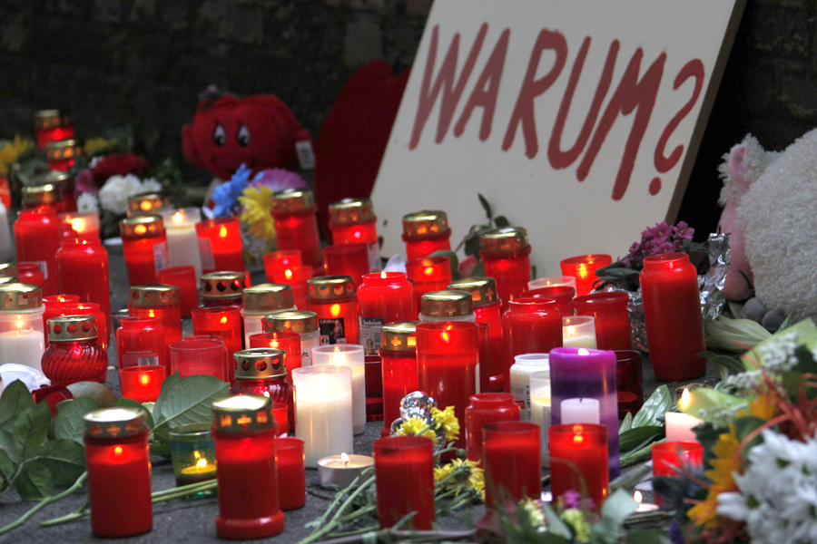 Flowers and candles are lying at the accident site in Duisburg, Germany, on Sunday, July 25, 2010, where more than a dozen died in a stampede at yesterday's Love Parade.The poster reads: Why?.(AP Photo/dapd/Mario Vedder)