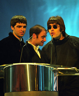 Oasis receive their 'Best British Newcomer' award from Kinks lead singer, Ray Davies. (L/R) Noel Gallagher, Paul McGuigan, Liam Gallagher, and Ray Davies.