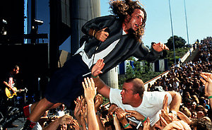 Eddie Vedder, frontman of American grunge group, jumps into the crowd during their performance on the Main Stage during the Lollapalooza Festival in 1992.