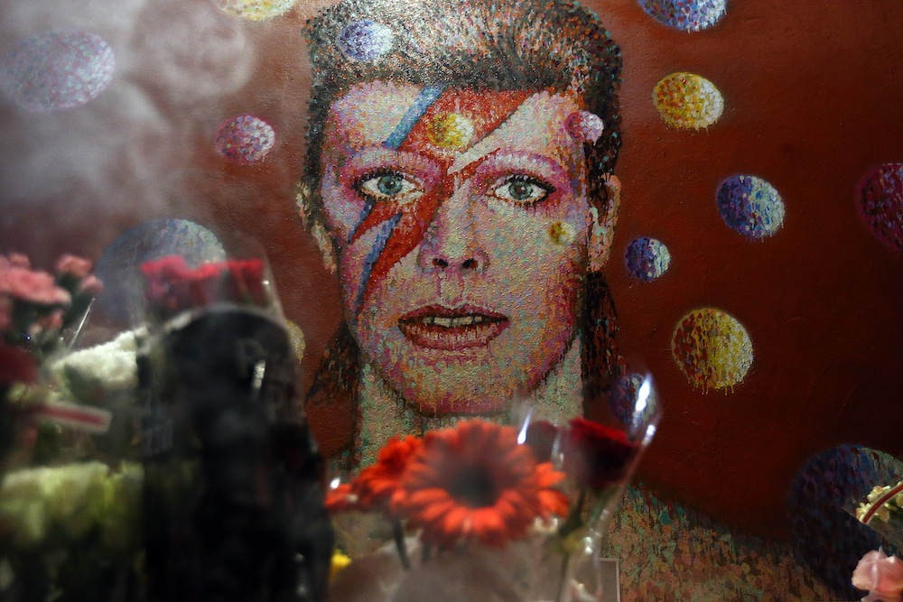 LONDON, ENGLAND - JANUARY 11: Flowers are laid beneath a mural of David Bowie in Brixton on January 11, 2016 in London, England. British music and fashion icon David Bowie died earlier today at the age of 69 after a battle with cancer. (Photo by Carl Court/Getty Images)