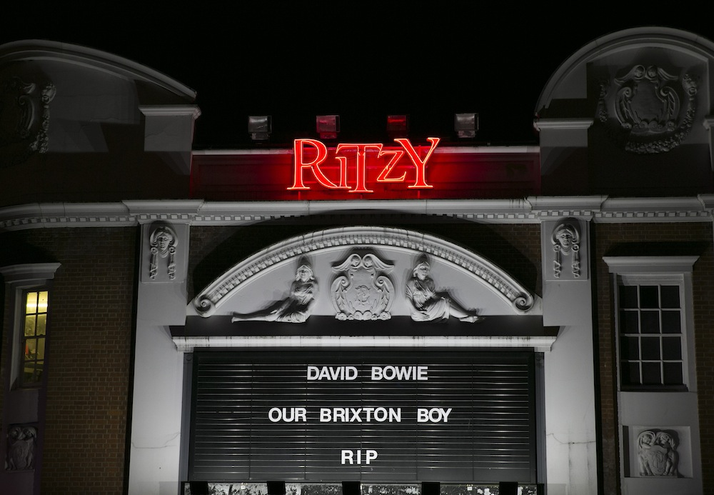 LONDON, ENGLAND - JANUARY 11:  A tribute to David Bowie is displayed outside Ritzy Cinema in Brixton on January 11, 2016 in London, England. British music and fashion icon David Bowie died earlier today at the age of 69 after a battle with cancer. on January 11, 2016 in London, England.  (Photo by John Phillips/Getty Images)