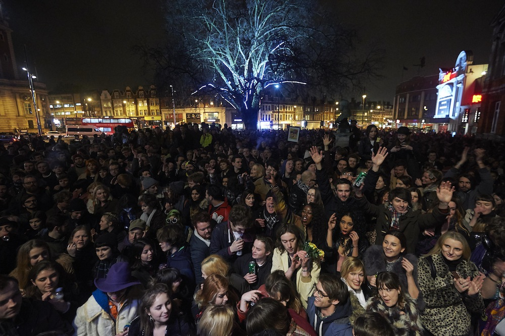 """Crowds gather outside the Ritzy cinema in south London to pay homage to British singer David Bowie following the announcement of Bowie's death on January 11, 2016. British music icon David Bowie died of cancer at the age of 69, drawing an outpouring of tributes for the innovative star famed for groundbreaking hits like """"Ziggy Stardust"""" and his theatrical shape-shifting style.   AFP PHOTO / NIKLAS HALLE'N / AFP / NIKLAS HALLE'N        (Photo credit should read NIKLAS HALLE'N/AFP/Getty Images)"""