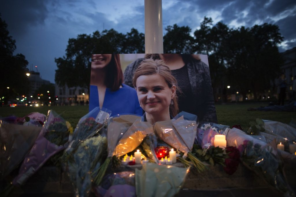 LONDON, UNITED KINGDOM - JUNE 16:  Flowers surround a picture of Jo Cox during a vigil in Parliament Square on June 16, 2016 in London, United Kingdom.  Jo Cox, 41, Labour MP for Batley and Spen, was shot and stabbed by an attacker at her constituicency today in Birstall, England. A man also suffered slight injuries during the attack. Jo Cox was reportedly shot and stabbed while holding her weekly surgery at Birstall Library, Birstall near Leeds and later died. A 52-year old man has been arrested in connection with the crime.  (Photo by Dan Kitwood/Getty Images)