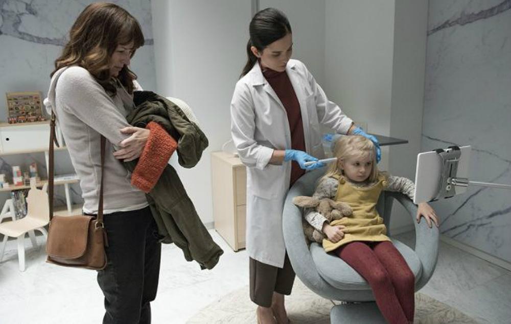 uma medica colocando um chip na cabeça da criança e a mãee olhando